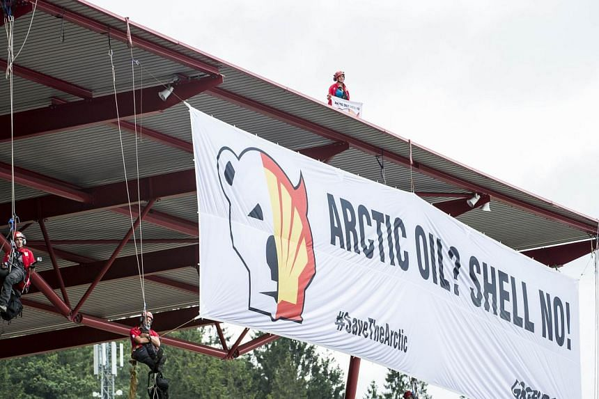"""Greenpeace militants deploy a banner reading """"ARCTIC OIL? SHELL NO!"""" during a protest against Shell, one of the main sponsors of the F1 Grand Prix, at the Spa-Francorchamps circuit in Spa on August 25, 2013 during the Belgium Formula One Grand Prix.&"""