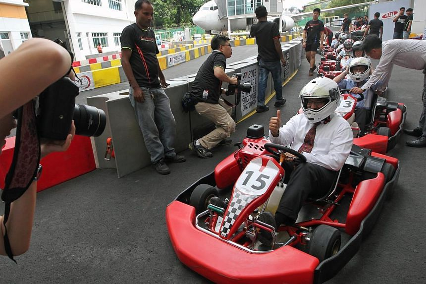 Mr S Iswaran, Minister in the Prime Minister's Office, Second Minister for Home Affairs and Second Minister for Trade and Industry, rides a go-kart at ITE COllege Central at an event to mark the five-year extension of a collaboration between ITE and