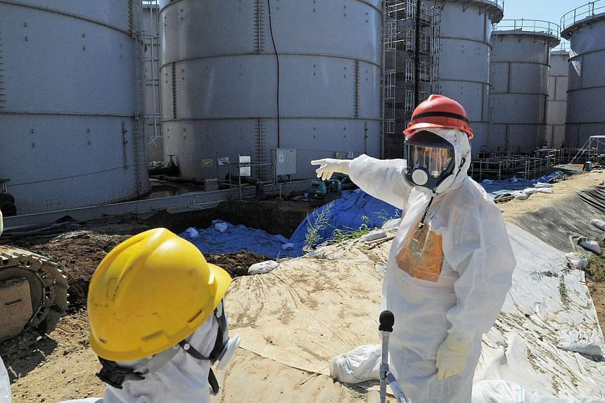 Japan's Economy, Trade and Industry Minister Toshimitsu Motegi (right), wearing a protective suit and a mask, inspects contaminated water tanks at the tsunami-crippled Fukushima Daiichi nuclear power plant in Fukushima on Monday, Aug 26, 2013. Japan'