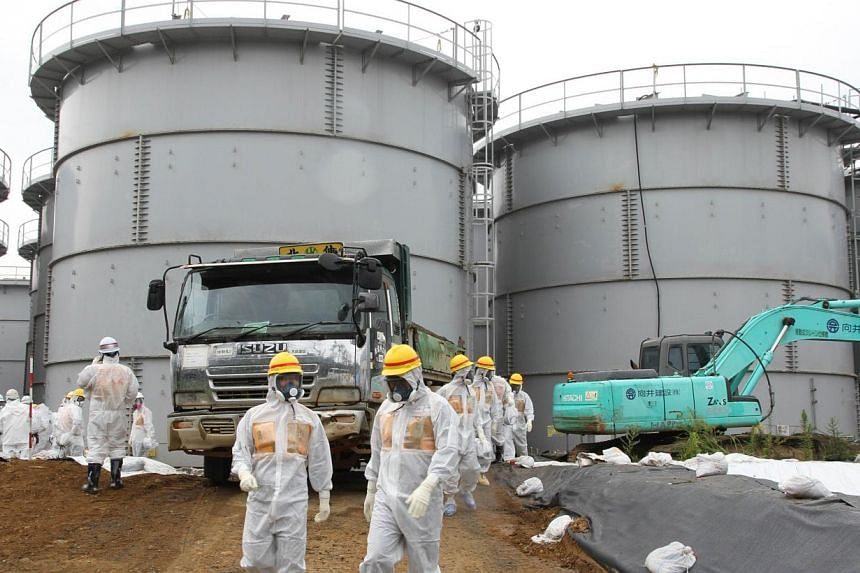 This handout picture taken by Japan's Nuclear Regulation Authority on Aug 23, 2013 shows nuclear watchdog members including Nuclear Regulation Authority members in radiation protection suits inspecting contaminated water tanks at the Tokyo Electric P