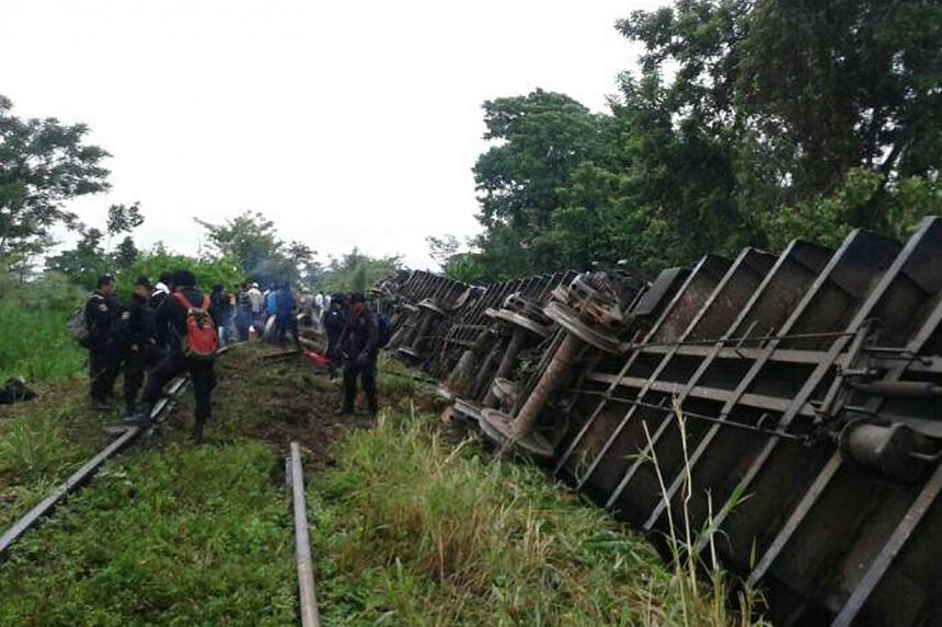 In this photo release by the Civil Protection of the State of Tabasco, police agents work at a site where a train derailed in Tabasco, Mexico, Sunday, Aug. 25, 2013. A cargo train carrying US-bound migrants derailed in a swampy area of south-eas