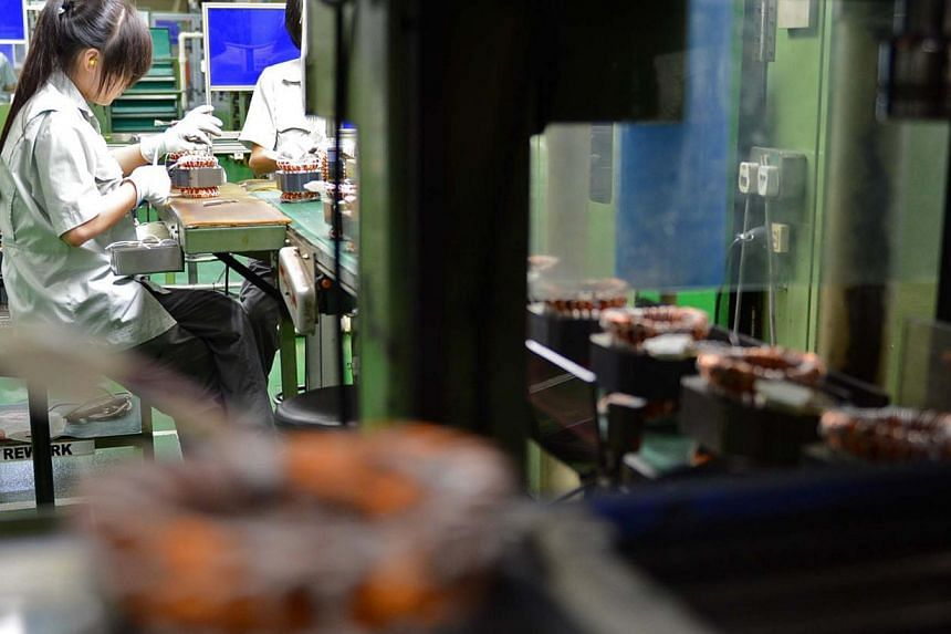 Employees working on a refrigerator compressor production line at the Panasonic factory in Bedok South. Singapore's industrial output gained 2.7 per cent last month over the same period last year, mainly boosted by the transport engineering and gener