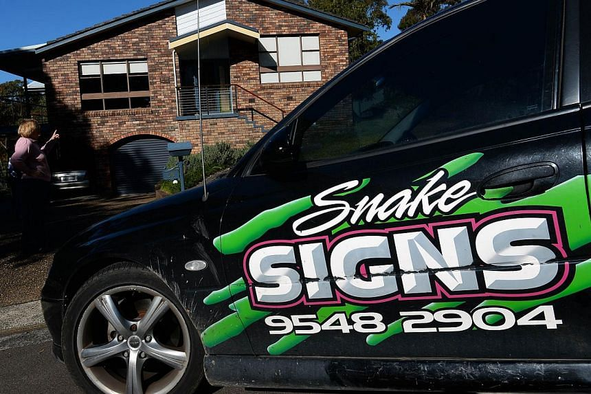 Resident Carolyn Bland (left) points to the whereabouts of snakes on her homes roof in Sydney on Aug 5, 2013.They are the nightmare tenants who can live undetected alongside Australian families for years: the world's deadliest snakes. -- FILE P