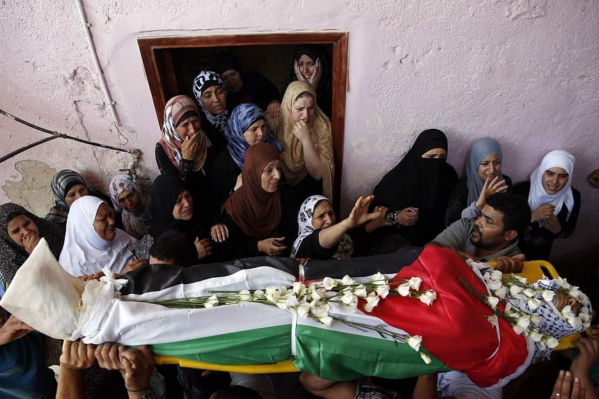 Palestinians carry the body of Jihad Aslan during his funeral at Qalandiya Refugee Camp near the West Bank city of Ramallah on MOnday, Aug 26, 2013. Peace talks between Israeli and Palestinian negotiators expected on Monday have been shelved after Is
