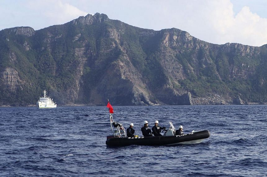 A Japan Coast Guard boat (front) and vessel sail as Uotsuri island, one of the disputed islands, called Senkaku in Japan and Diaoyu in China, is pictured in the background, in the East China Sea on Aug 18, 2013. China sees no basis to conduct talks w