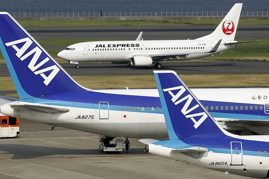 All Nippon Airways' (ANA) aeroplanes at Haneda airport in Tokyo on Aug 8, 2013. Japan's ANA Holdings Inc will buy a 49 per cent stake in Myanmar carrier Asian Wings Airways as part of a strategy to expand overseas by investing in airline related busi