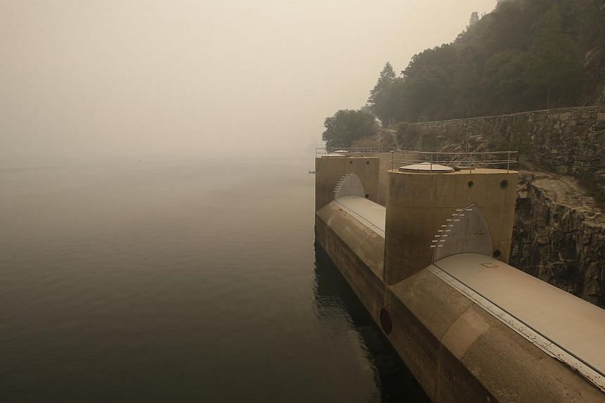 In this Sunday, Aug 25, 2013, photo, the Hetch Hetchy Reservoir is hazy with smoke from the Rim Fire fills the air in Yosemite National Park, California. Firefighters reported progress Monday battling a huge blaze on the edge of Yosemite National Par