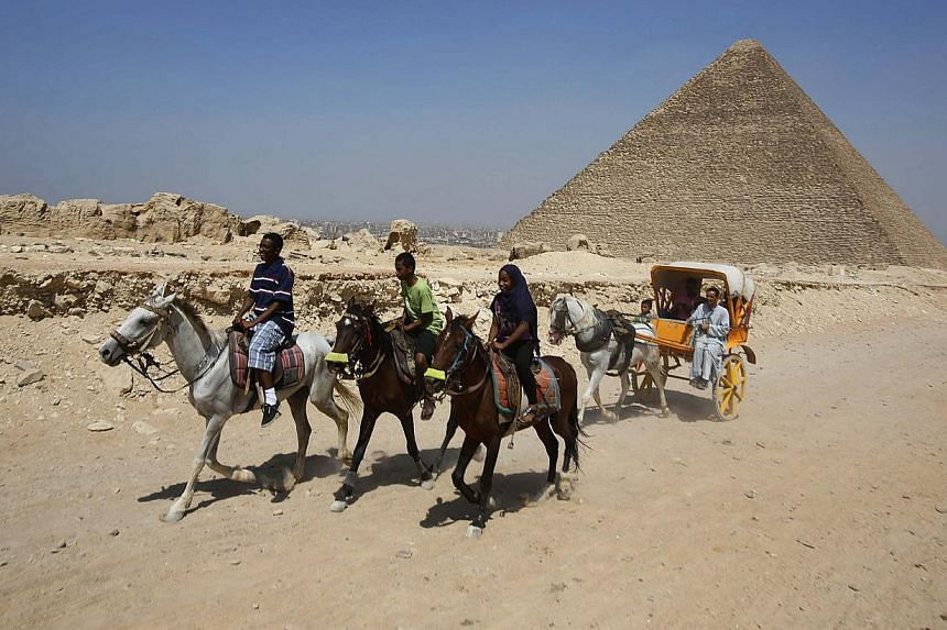 Egyptian tourists ride on horses at the Giza Pyramids, on the outskirts of Cairo on Aug 26, 2013. International tourist numbers surged by 5.2 percent to nearly half a billion people worldwide in the first half of 2013, beating earlier expectations, t