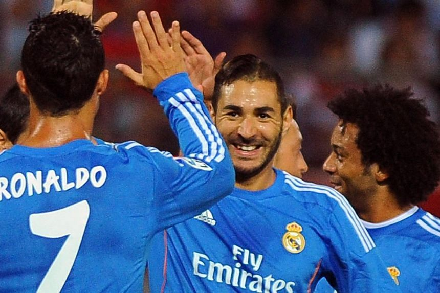 Real Madrid's French forward Karim Benzema (centre) celebrates with his teammates after scoring during the Spanish league football match Granada FC vs Real Madrid CF at Nuevo Los Carmenes stadium in Granada on Aug 26, 2013. Real made it two wins from