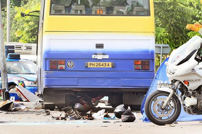 A motorcyclist died after allegedly being hit by a holiday coach and dragged for five metres across the road. He is believed to be a Malaysian in his 40s. -- PHOTO: SHIN MIN