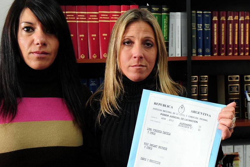 Virginia Luna (right), lawyer of Argentine women in the lawsuit for defective Poly Implant Prothese (PIP) French-made breast implants, beside Gabriela Albela (left), the plaintiff in that case, shows the lawsuit in her office at the district courts d