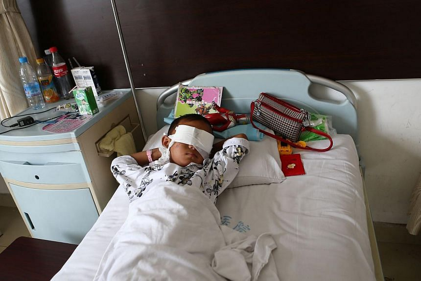 A boy lies on his hospital bed with his eyes covered with bandages in a hospital in Taiyuan, north China's Shanxi province on Tuesday, Aug 27, 2013. The six-year-old had his eyes gouged out, blinding him for life, in a gruesome attack that may have b