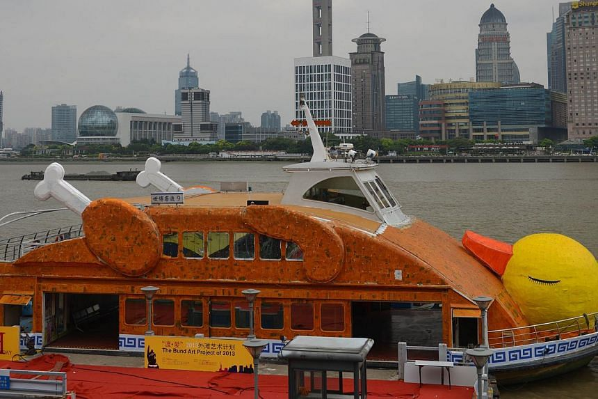 """Shanghai's """"roasted"""" version of Dutch artist Florentijn Hofman's giant yellow duck, complete with drumsticks and crispy brown skin, floatson the Huangpu River in Shanghai onTuesday, Aug 27, 2013.Not to be outdone by Hong Kong, where"""