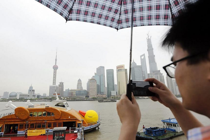 """A man takes a photo of Shanghai's """"roasted"""" version of Dutch artistFlorentijn Hofman's giant yellow duckin Shanghai onTuesday, Aug 27, 2013.Not to be outdone by Hong Kong, where Hofman's 16.5m-tallRubber Duck installatio"""