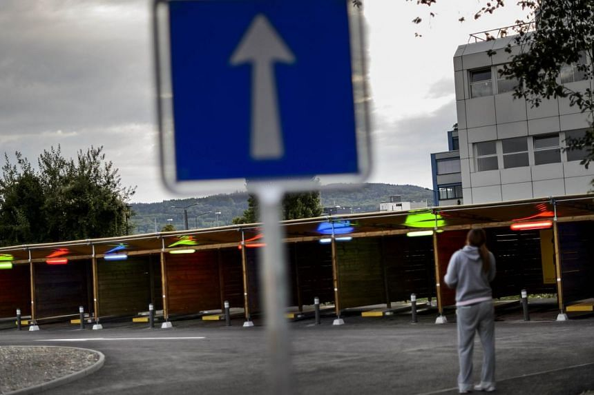 """A woman faces the so-called """"sex boxes"""" at the opening day of Switzerland's first sex drive-in on Aug 26, 2013 in Zurich, which is aiming to get prostitution off the city streets. The sex drive-in opened for business on Monday to a big fanfare, but f"""