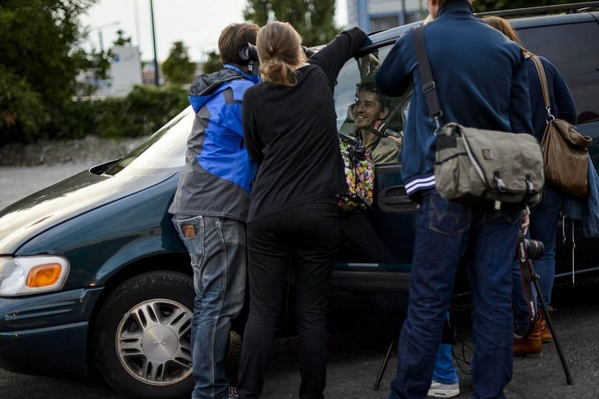 Journalists surround a visitor on the opening day of Switzerland's first sex drive-in on Aug 26, 2013, in Zurich, which is aiming to get prostitution off the city streets.The sex drive-in opened for business on Monday to a big fanfare, but few