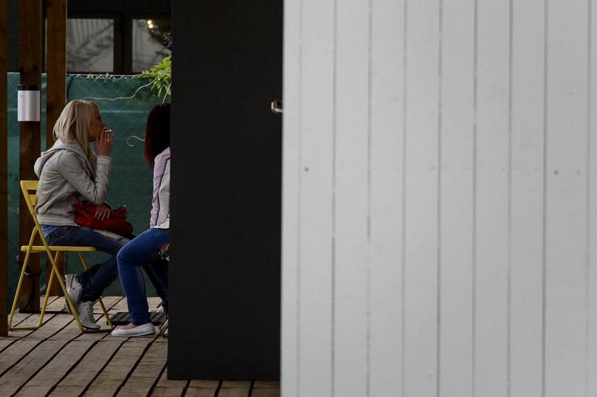 Two women wait on the opening day of Switzerland's first sex drive-in on Aug 26, 2013 in Zurich, which is aiming to get prostitution off the city streets. The sex drive-in opened for business on Monday to a big fanfare, but few customers. -- PHOTO: A