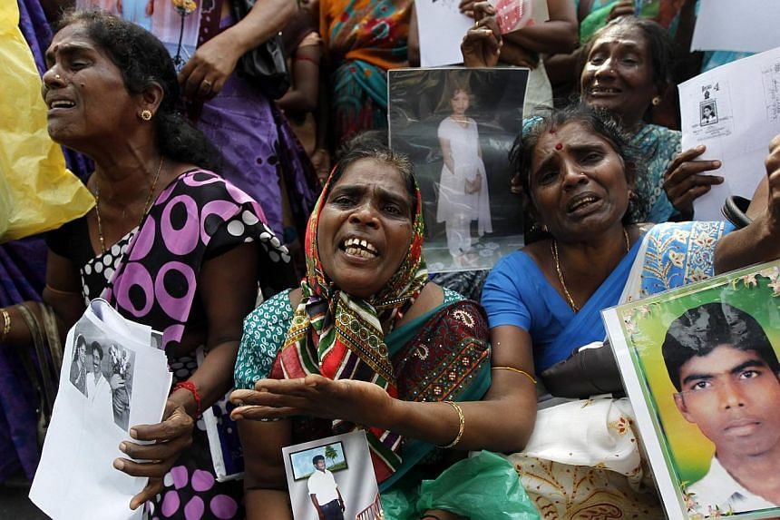 Tamil women cry as they hold up images of their missing family members at a protest in Jaffna on Tuesday, Aug 27, 2013. Protesters in Sri Lanka criticised the United Nations for a second day on Tuesday during a visit by UN Human Rights Commissioner N