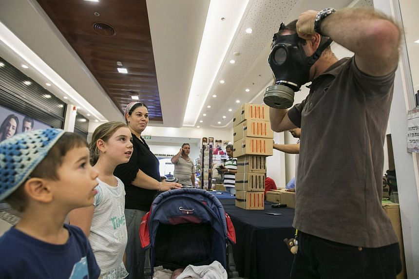 An Israeli man shows his children how to adjust a gas mask at a distribution point at a shopping mall in the West Bank Jewish settlement of Maale Adumim, near Jerusalem on Monday, Aug 26, 2013.Fearing a possible US strike against neighbouring S