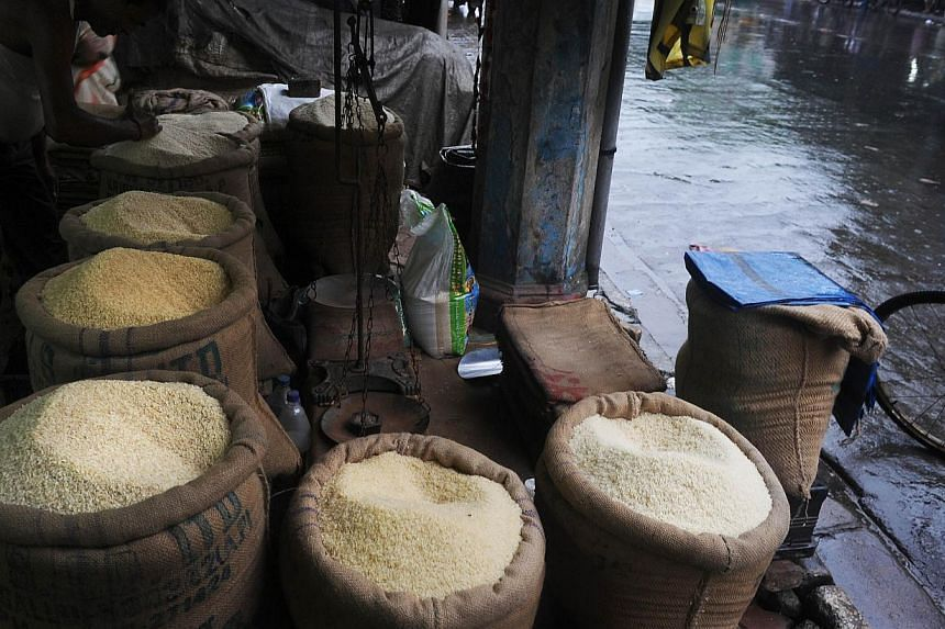 An Indian rice vendor prepares of rice sacks in his roadside shop on a pavement in Kolkata on Aug 26, 2013. India's parliament on Monday passed a flagship US$18 billion (S$23 billion) programme to provide subsidised food to the poor that is int