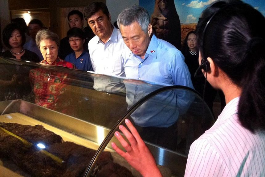 Prime Minister Lee Hsien Loong, flanked by Mrs Lee and Xinjiang chairman Nur Bekri, looking at a 3,800-year old female mummy, during his tour of the Xinjiang Ugyhur Autonomous Region Museum in Urumqi capital on Tuesday morning. -- ST PHOTO: KOR KIAN