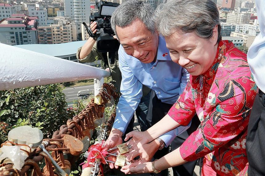 Prime Minister Lee Hsien Loong and wife Ho Ching leave their love locks in Hongshan Park in Xinjiang's capital Urumqi on Tuesday, Aug 27, 2013. Lovers observe a local custom where they lock a pair of padlocks together onto a hillside fence and then h