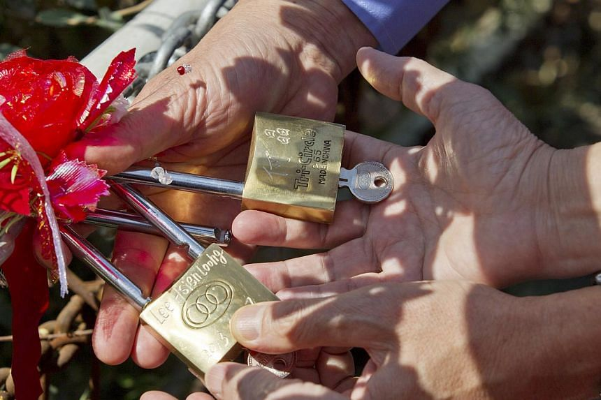 Prime Minister Lee Hsien Loong and wife Ho Ching leave their love locks in Hongshan Park in Xinjiang's capital Urumqi on Tuesday, Aug 27, 2013. The locks have their names printed on them. Lovers observe a local custom where they lock a pair of padloc