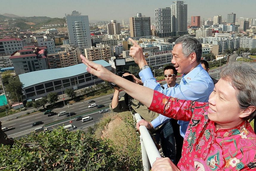 Prime Minister Lee Hsien Loong and wife Ho Ching throw away the keys of their love padlocks in Hongshan Park in Xinjiang's capital Urumqi on Tuesday, Aug 27, 2013. Lovers observe a local custom where they lock a pair of padlocks together onto a hills