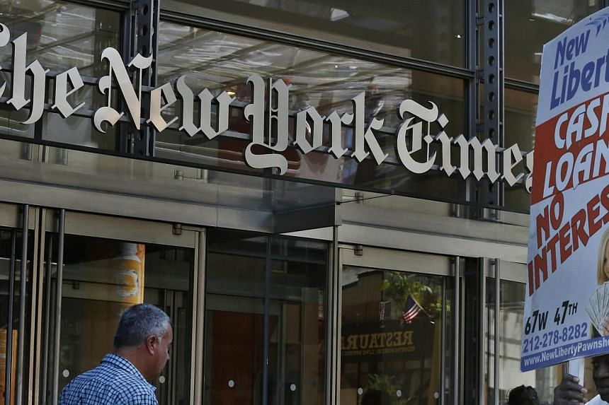 People walk past the New York Times Building in New York on Aug 14, 2013. The website of The New York Times experienced another outage on Tuesday afternoon, likely caused by hackers, the company said. -- FILE PHOTO: REUTERS