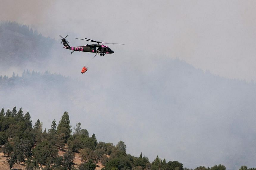 A California Army National Guard UH-60 Black Hawk helicopter assists in fighting a massive wildfire near Yosemite National Park in this handout photo taken on Aug 23, 2013. The wildfire threatening Yosemite National Park grew on Aug 27 to become the