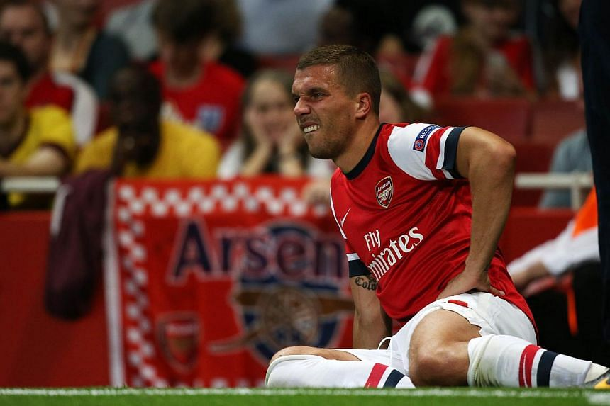 Arsenal's Polish-born German striker Lukas Podolski lies injured on the sideline before being stretchered off during the Uefa Champions League Play-Off second leg football match at The Emirates Stadium in north London on Aug 27, 2013. Arsenal manager