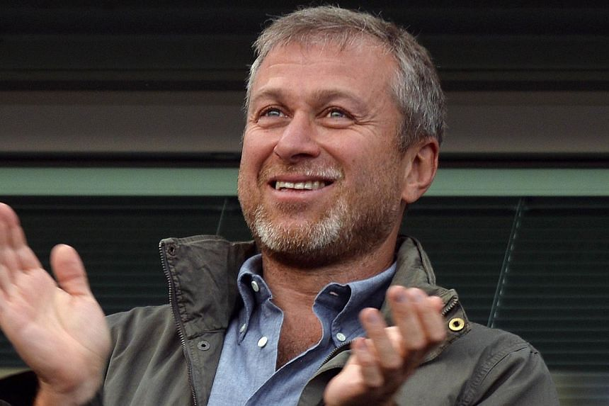 Chelsea owner Roman Abramovich applauds after the English Premier League football match between Chelsea and Hull City at Stamford Bridge in London on Aug 18, 2013. Mr Abramovich has decided to wind up his Russian football development programme that s