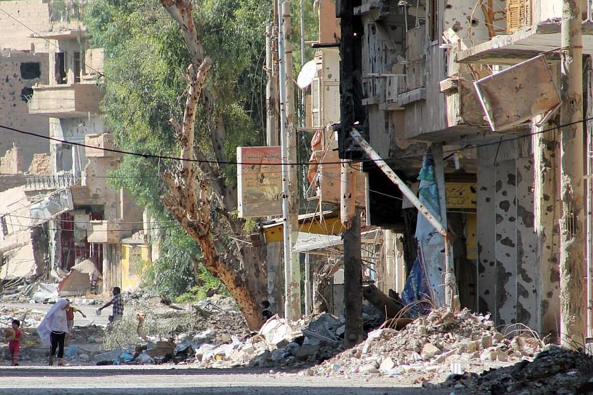Syrians walk in a heavily damaged street in Syria's eastern town of Deir Ezzor on Monday, Aug 26, 2013.British Prime Minister David Cameron's office said on Wednesday, Aug 28, 2013, that he and US President Barack Obama had no doubt Syrian Pres