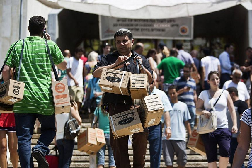 Israelis carry their old gas mask kits in order to replace them for new ones as others leave with new gas mask kits at a distribution point in Tel Aviv on Wednesday, Aug 28, 2013. Israel is deploying all of its missile defences as a precaution agains