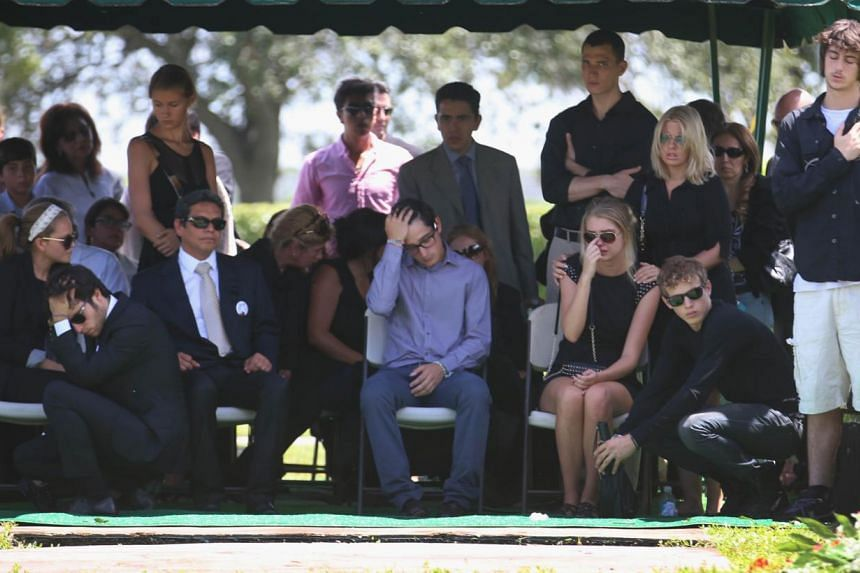 Family and friends sit near the burial plot after the internment of 18-year-old graffiti artist Israel Hernandez-Llach at the Vista Memorial Gardens & Funeral Home, after he died when he was Tasered by a Miami Beach police officer on Aug 14, 2013
