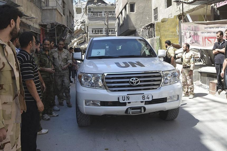 Free Syrian Army fighters and residents gather around a convoy of United Nations (UN) vehicles carrying a team of UN chemical weapons experts at one of the sites of an alleged chemical weapons attack in Damascus' suburbs of Zamalka on Wednesday,