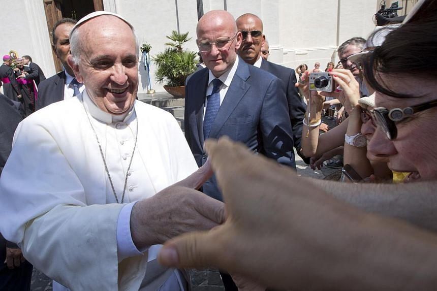 Pope Francis greets the faithful as he leaves the village of Castel Gandolfo, the pontiffs' summer residence in the hills overlooking Rome on Thursday, Aug 15, 2013. Pope Francis has phoned an Argentine woman to comfort her and tell her she is n