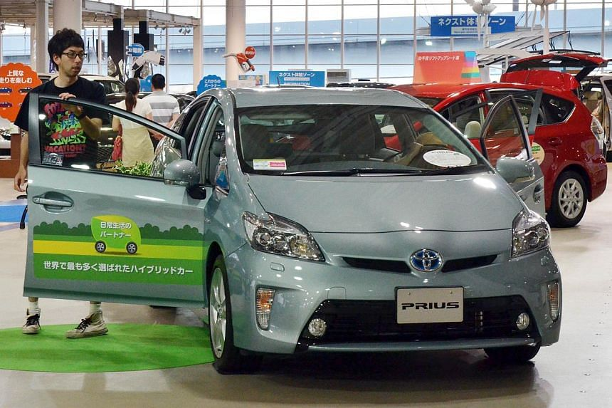 A customer looks at Toyota Motor's popular hybrid vehicle Prius at a showroom in Tokyo on July 3, 2013. Toyota Motor Corp, which introduced most consumers to hybrid technologies with its Prius more than 15 years ago, said on Wednesday that the next g