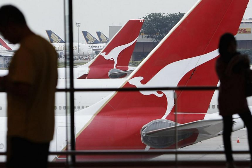 A woman looks at Qantas planes sitting on the tarmac at a viewing gallery at Singapore's Changi Airport on Aug 20, 2013. Australian flag carrier Qantas bounced back into the black Thursday, posting an annual net profit of A$5 million (S$5.7 million),