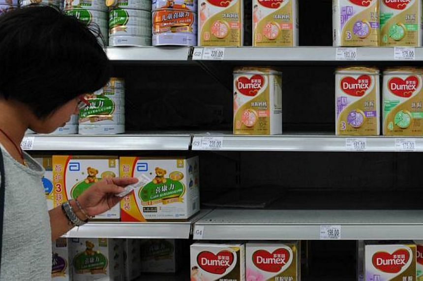 A woman checks the price tag beside a shelf of Dumex baby formula, which uses the New Zealand dairy Fonterra as its raw material supplier, at a store in Yichang, in central China's Hubei province on on Aug 5, 2013. New Zealand demanded answers on how