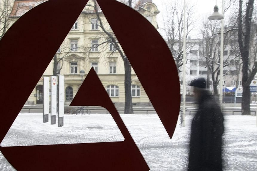 A man walks behind the sign of an unemployment centre in Munich on Jan 29, 2009.German unemployment registered a small unexpected rise in August, due to a scaling back of job creation schemes, but the labour market overall remains stable, offic