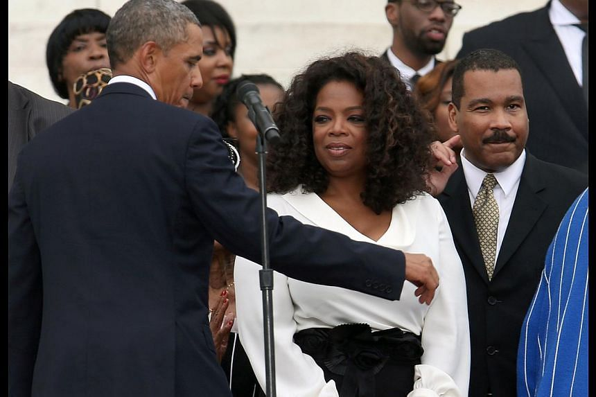 President Barack Obama (left) and Oprah Winfrey greet members of the King family during the ceremony to commemorate the 50th anniversary of the March on Washington for Jobs and Freedom on Aug 28, 2013 in Washington, DC. -- PHOTO: AFP