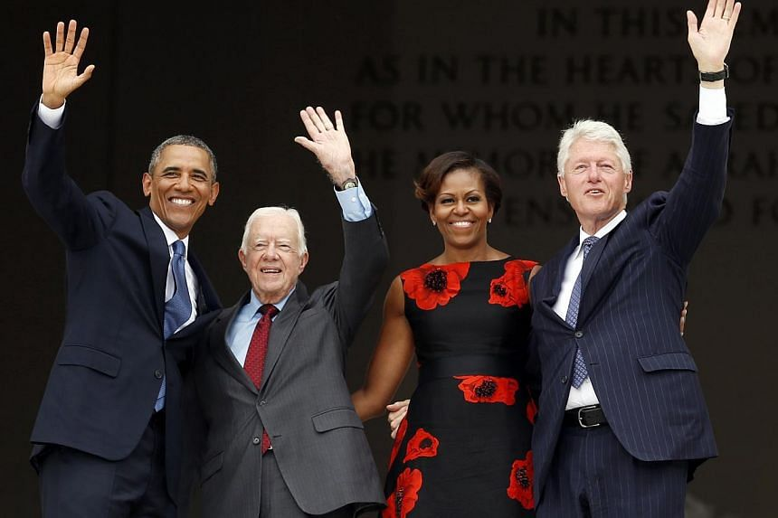 (Left to right) US President Barack Obama, former President Jimmy Carter, first lady Michelle Obama and former President Bill Clinton wave from the steps of the Lincoln Memorial during the commemoration ceremony for the 50th anniversary of the March