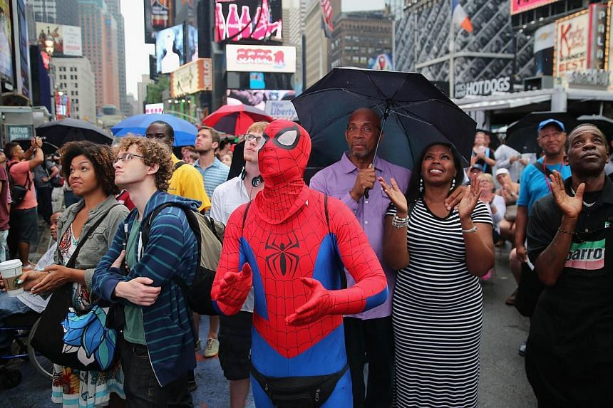"A crowd watches a giant screen in Times Square as U.S. President Barack Obama speaks on the 50th anniversary of Martin Luther King Jr.'s ""I Have a Dream"" speech on Aug 28, 2013 in New York City. -- PHOTO: AFP"
