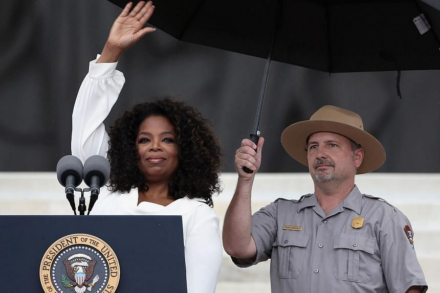 """Talk show host Oprah Winfrey (left) speaks during the Let Freedom Ring ceremony at the Lincoln Memorial on Aug 28, 2013 in Washington, DC. The event was to commemorate the 50th anniversary of Dr Martin Luther King Jr.'s """"I Have a Dream"""" speech and th"""