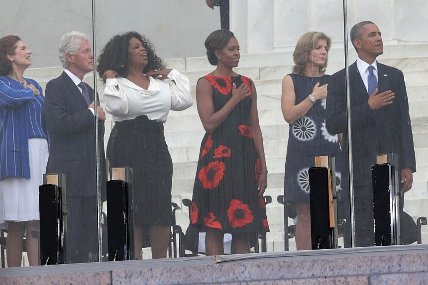 (Right to left) US President Barack Obama, Caroline Kennedy, first lady Michelle Obama, former talk show host Oprah Winfrey, former president Bill Clinton and Lynda Bird Johnson Robb listen to the National Anthem during the Let Freedom Ring ceremony