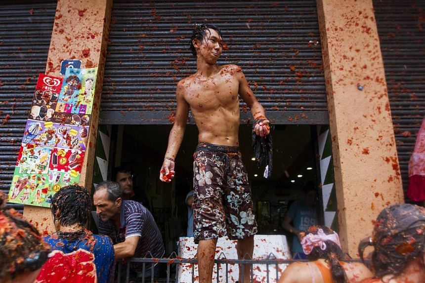 """Revellers take part in the annual """"Tomatina"""" festivities in Buñol, near Valencia, on Aug 28, 2013. Some 20,000 revellers pelted each other with tonnes of squishy tomatoes in Spain's annual tomato fight on Wednesday - but this year they had to pay to"""