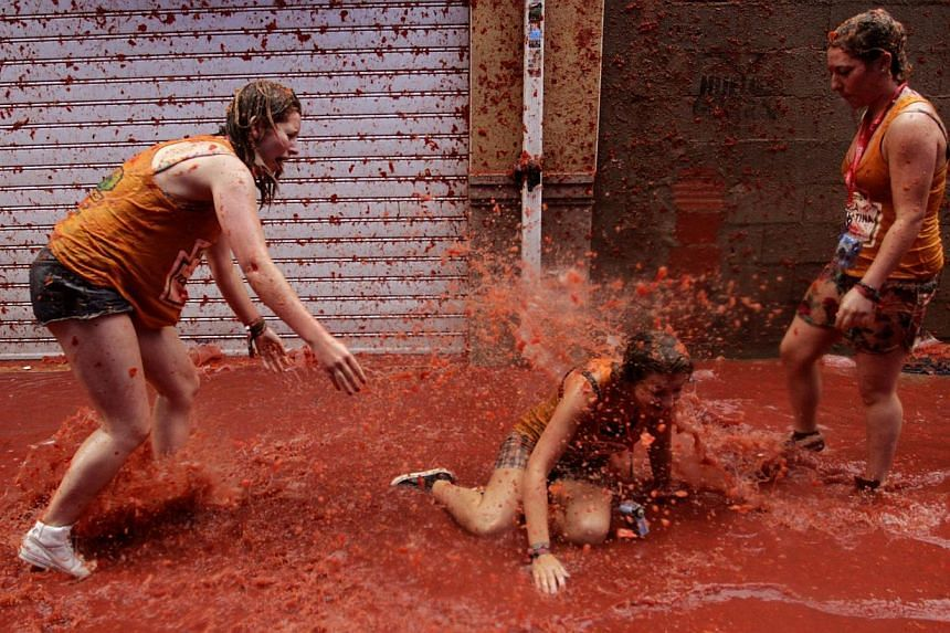 """Revellers play in tomato pulp after the annual """"Tomatina"""" in the Mediterranean village of Buñol, near Valencia, on Aug 28, 2013. Some 20,000 revellers pelted each other with tonnes of squishy tomatoes in Spain's annual tomato fight on Wednesday - bu"""