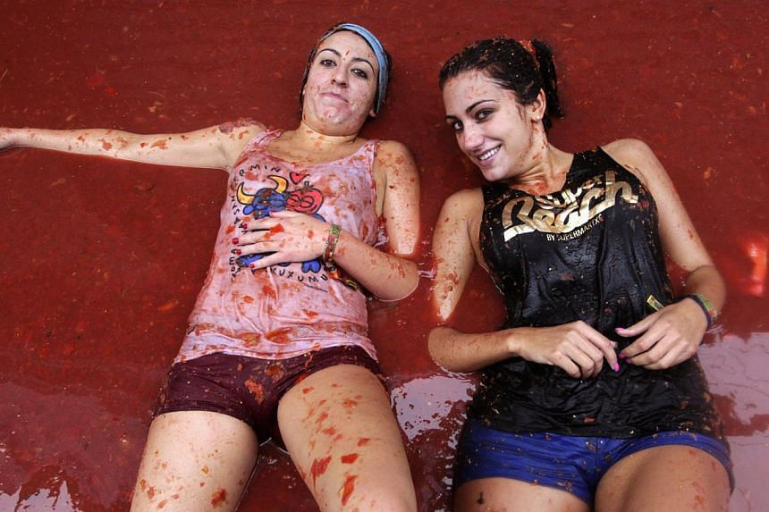 """Revellers lie in tomato pulp after the annual """"Tomatina"""" (tomato fight) in the Mediterranean village of Buñol, near Valencia, Aug 28, 2013. Some 20,000 revellers pelted each other with tonnes of squishy tomatoes in Spain's annual tomato fight on Wed"""