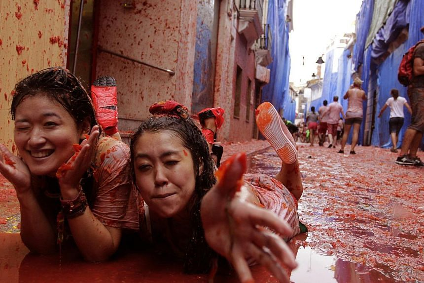 """Revellers lie in tomato pulp after the annual """"Tomatina"""" (tomato fight) in the Mediterranean village of Buñol, near Valencia, on Aug 28, 2013. Some 20,000 revellers pelted each other with tonnes of squishy tomatoes in Spain's annual tomato fight on"""